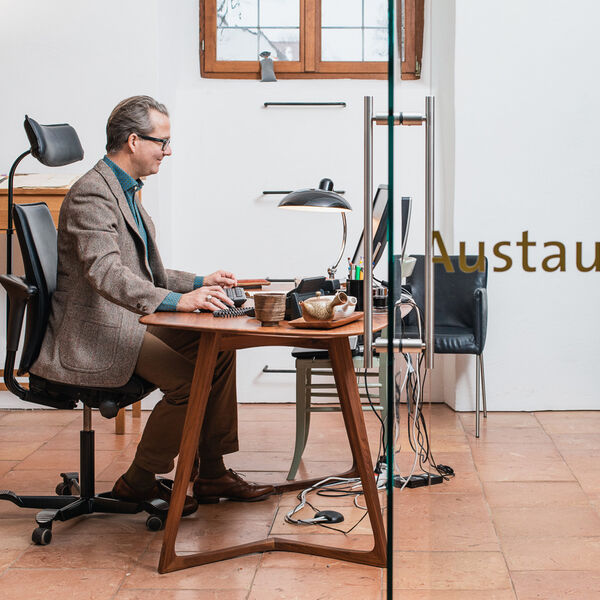 View into the office of Alexander Karl Wandinger. The director of the Trachten Information Centre is presented in side profile, working at his wooden desk at the computer with a smile.