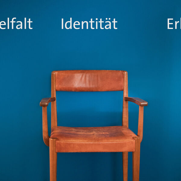 "A simple antique wooden chair with a brown leather seat stands in front of a blue wall in the premises of the Trachten Information Centre. In white above it, ""diversity"" and ""identity"", two words of a longer wall print, can be read."