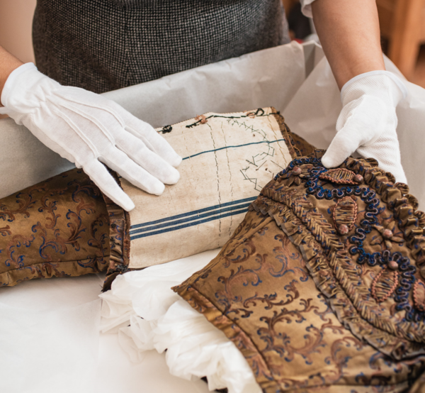 Wearing white gloves, an archivist wraps a historic golden silk bodice in tissue paper.