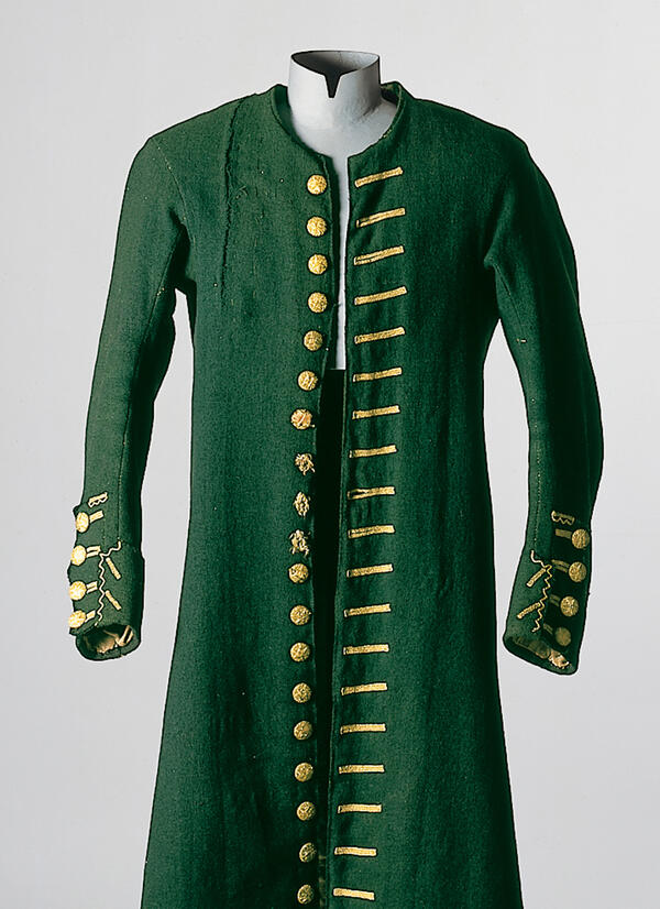"A dress-up doll presents a ""Justacorps"" in the colour forest green with golden buttons and decorated buttonholes. The garment for men origins from Lenggries, and is dated around 1810."
