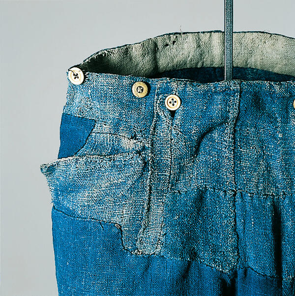 Detail of indigo dyed linen trousers, which has been patched several times. These working trousers are dated about 1850 and originate from Munich.