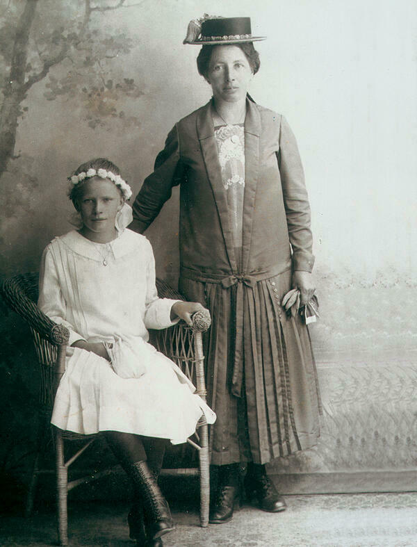 This black-and-white photograph from Attenberg, dated 1925/30, shows a girl in a confirmation dress, sitting on a wicker chair next to her festively dressed mother who stands close to her with one hand resting on the child's shoulder. Both are tenderly smiling into the camera. Behind them a landscape wallpaper is visible.