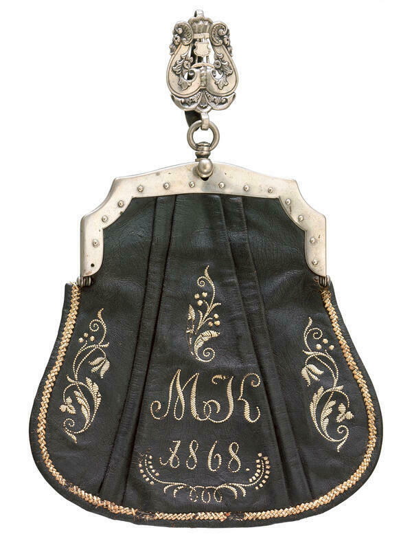 The Upper Bavarian waitress bag from 1868 is made of black leather. The front shows a monogram with the initials MK, which was embroidered with the quill, as well as the year and decorative patterns. The buckle and suspension of the bag are made of silver-plated bronze.