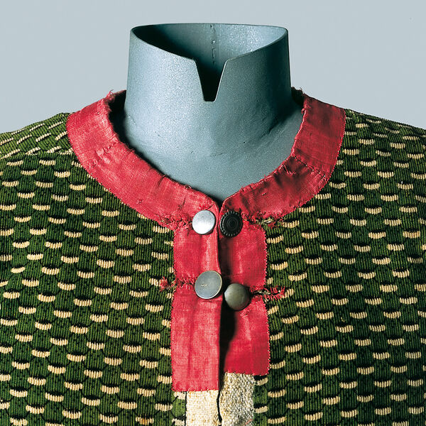 The dress-up doll wears a green patterned linen camisole from the Isarwinkel around 1800. Collar and neckline are made of red silk velvet, closed by two rows of metal buttons.