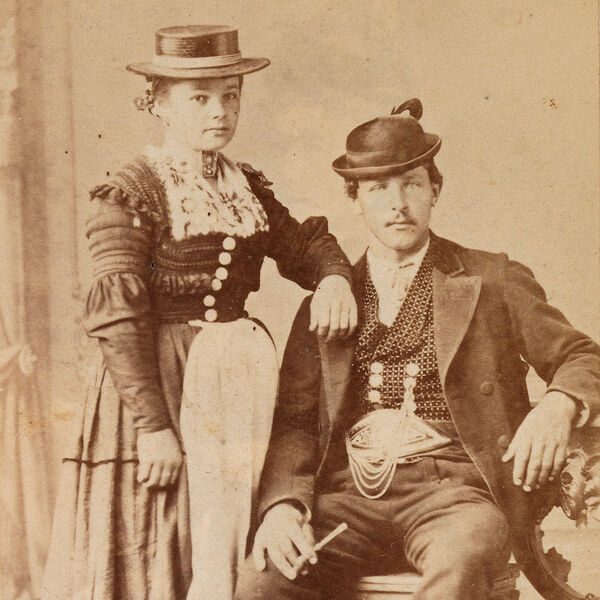 The sepia toned photograph shows a young farmer couple from the Rupertiwinkel around 1875 in festive costume. The man is sitting right beside the woman, whose arm rests on his shoulder.