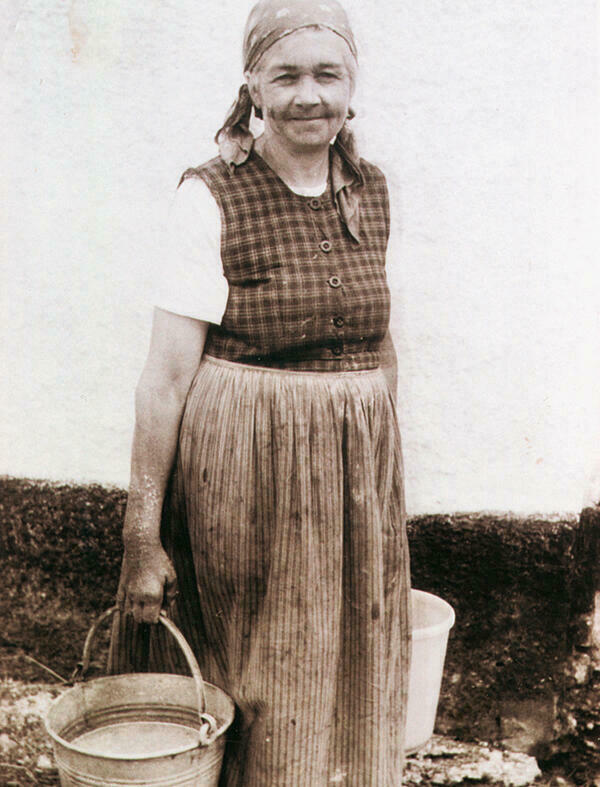 The black-and-white photograph shows a smiling older peasant woman from Rehling around 1950/60. She is wearing a patterned work dress, a short-sleeved white blouse underneath, a headscarf and holds a bucket in each hand.