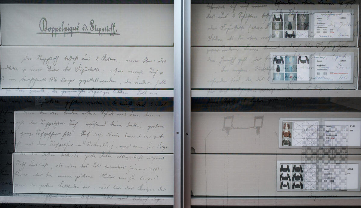 Closeup view of storage boxes made of grey cardboard stacked in the metal archive shelves at the Trachten Information Centre of the District of Upper Bavaria.