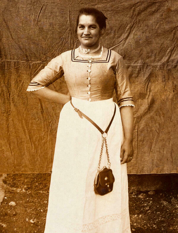 Black and white photograph of an Upper Bavarian waitress around 1910. The waitress's bag hangs on the belt of the dirndl in her waistcoat.