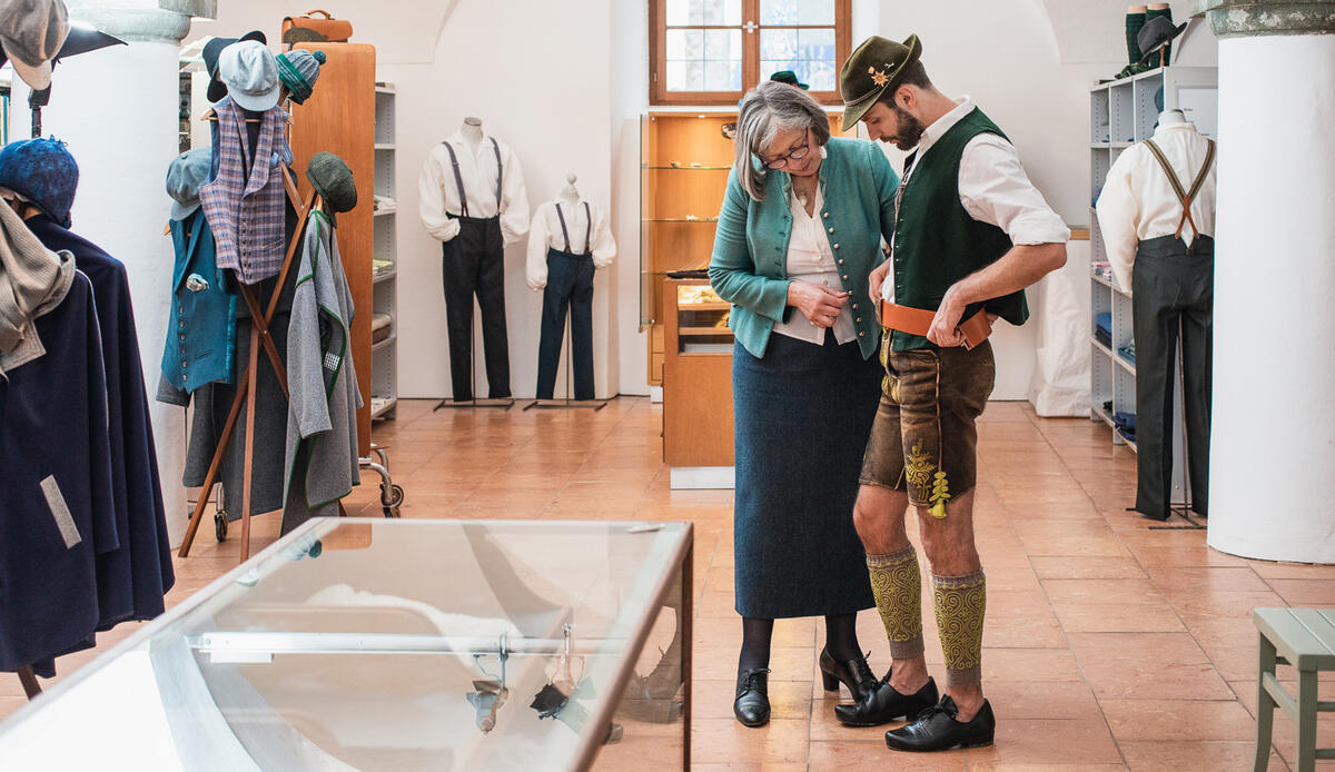 At the Trachten-Kontor of the Trachten Information Centre a female employee fits a young man in traditional costume - he wears a hat, waistcoat and leather trousers, loferls and Haferl shoes - with a leather belt.